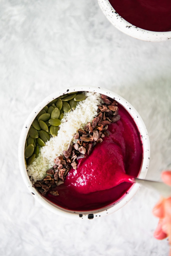 A spoonful of berry beet smoothie bowl being lifted out of a full bowl perfectly topped with cacao nibs, shredded coconut and pumpkin seeds.