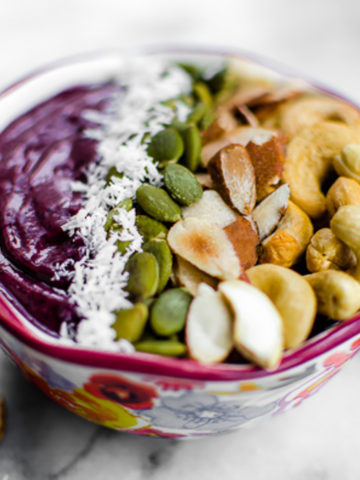 A purple smoothie bowl topped with shredded coconut, pumpkin seeds, toasted almonds and cashews.