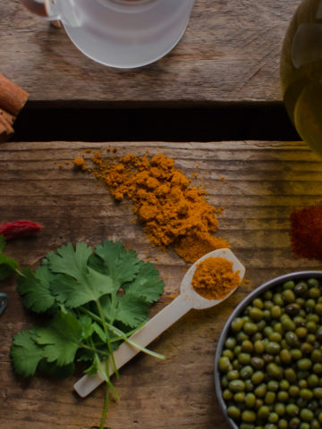 a spoonful of turmeric powder spilled on a rustic wooden surface surrounded by fresh parsley, cinnamon sticks, a bowl of mung beans, a pile of paprika and a bottle of olive oil.
