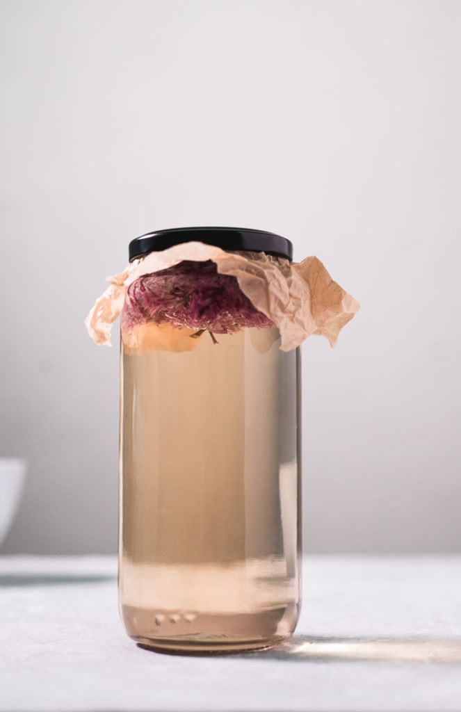 A jar filled with white wine vinegar and chive blossoms floating at the top, covered with a piece of parchment paper, sealed on underneath the lid.