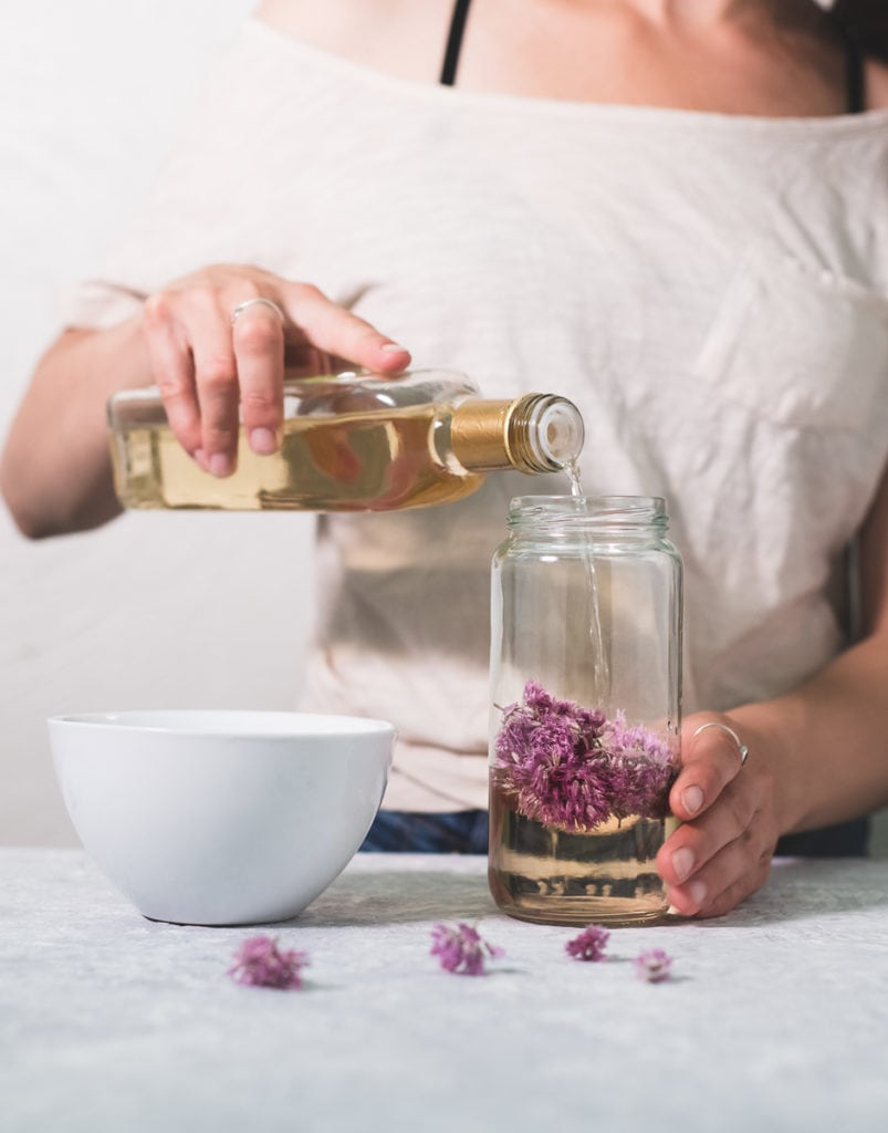 A person pouring white wine vinegar over chive blossoms in a jar, a white bowl sitting to the side and a few chive flowers sprinkled in front.