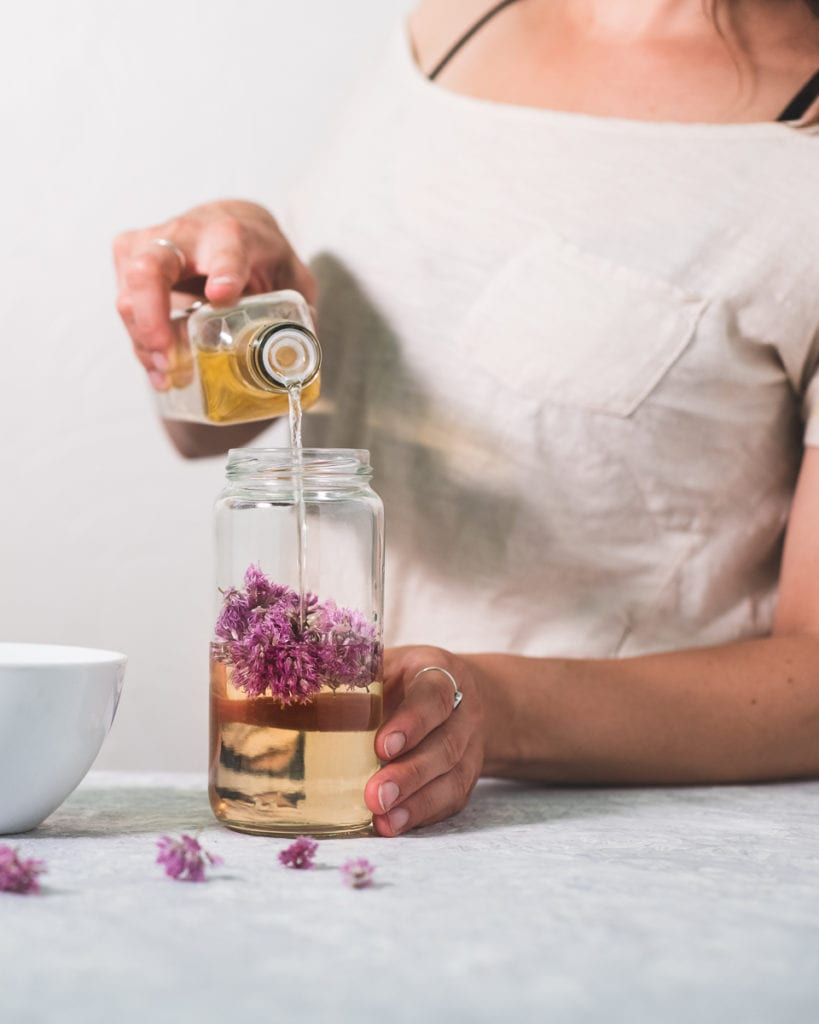Person standing on an angle, pouring white wine vinegar into a jar with chive blossoms in it, a bowl to the side and a few chive flowers sprinkled about in front.