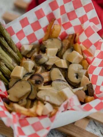 A hearty vegan poutine with mushroom, creamy gravy and roasted asparagus in a bowl lined with checkered red and white wax paper.