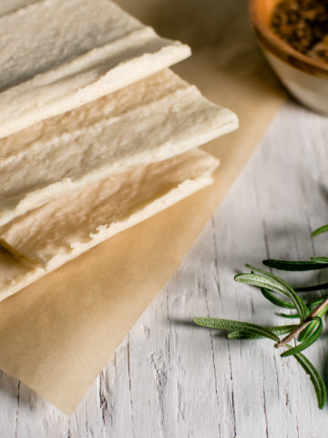 A stack of grain-free flatbread sitting on a piece of natural parchment paper and a sprig of rosemary placed beside.
