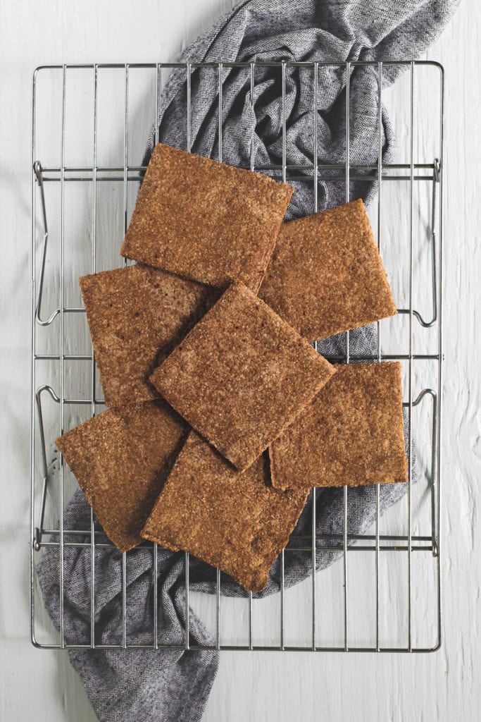 Graham Crackers laying flat on a cooling wrack, sitting on top of a bunched up linen cloth