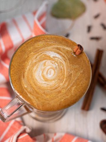 A frothy, creamy Vegan Pumpkin Spice Latte swirled with cashew cream as a garnish.