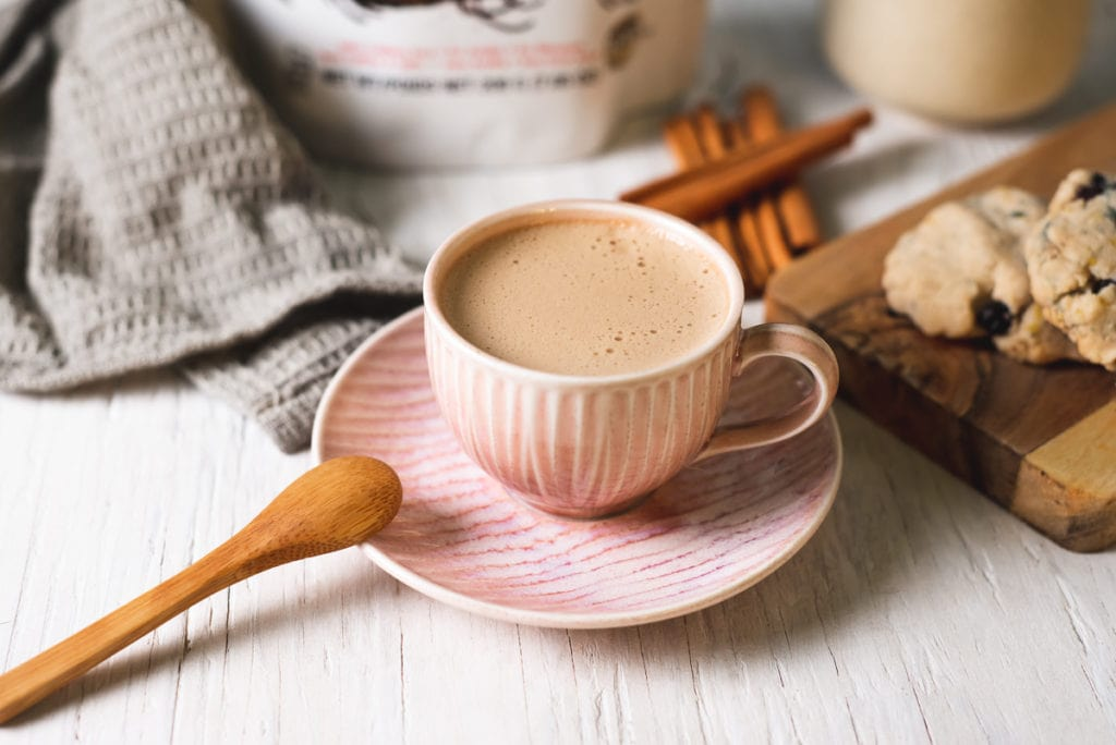 A frothy dairy-free cinnamon latte in a pink tea up surrounded by cinnamon sticks a bag of dandy blend a linen cloth and cookies.