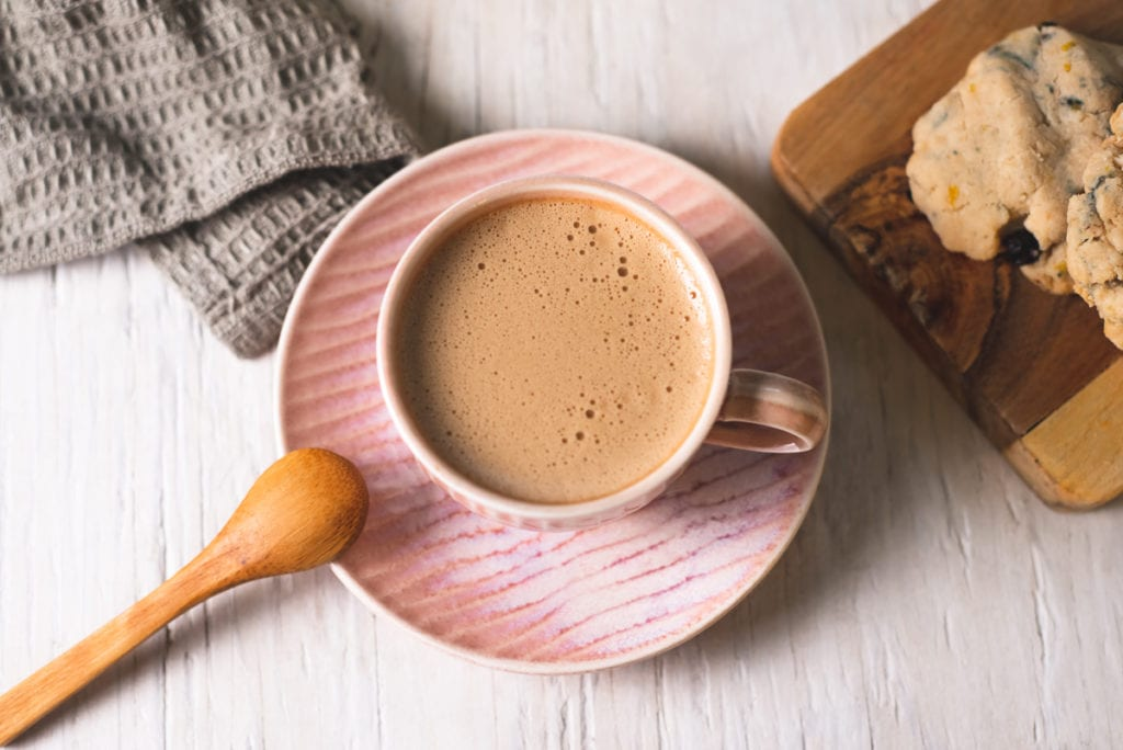 A nice, frothy cinnamon latte in a pink mug with a little wooden spoon, cookies and a cloth napkin surrounding.