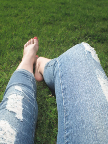 A woman's legs, dressed in ripped jeans sitting barefoot on the ground.
