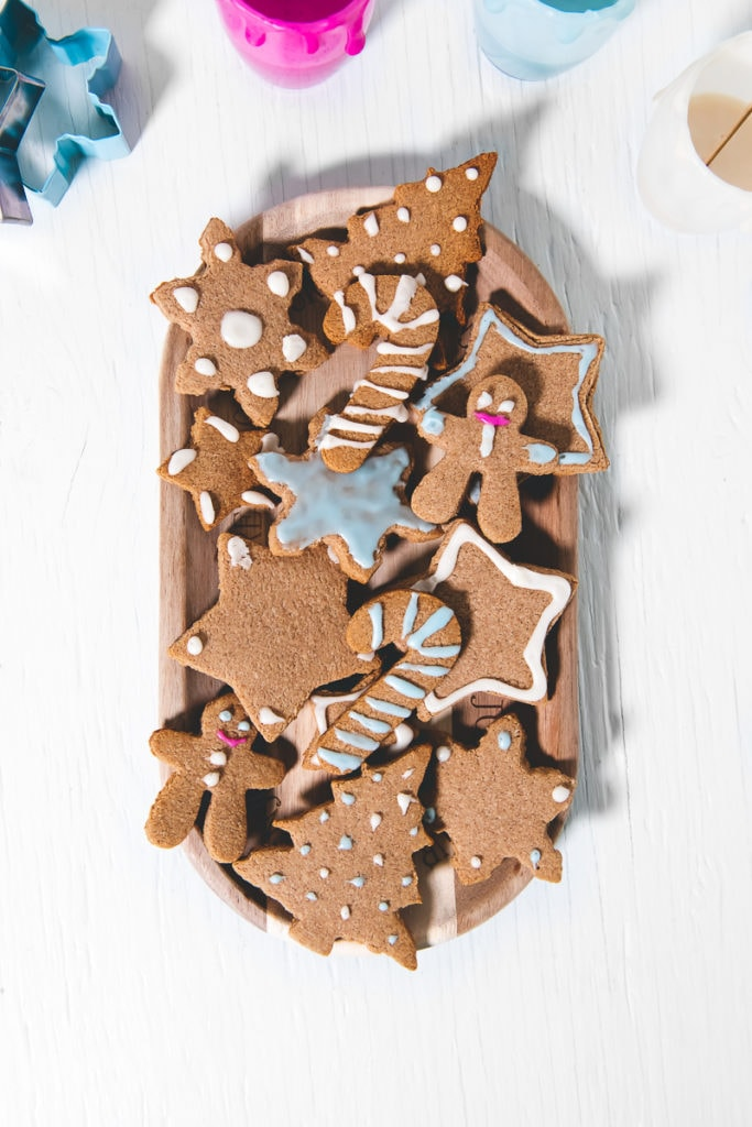 A plate full of Crunchy gluten-free vegan Gingerbread Cookies decorated with Eggless Royal Icing
