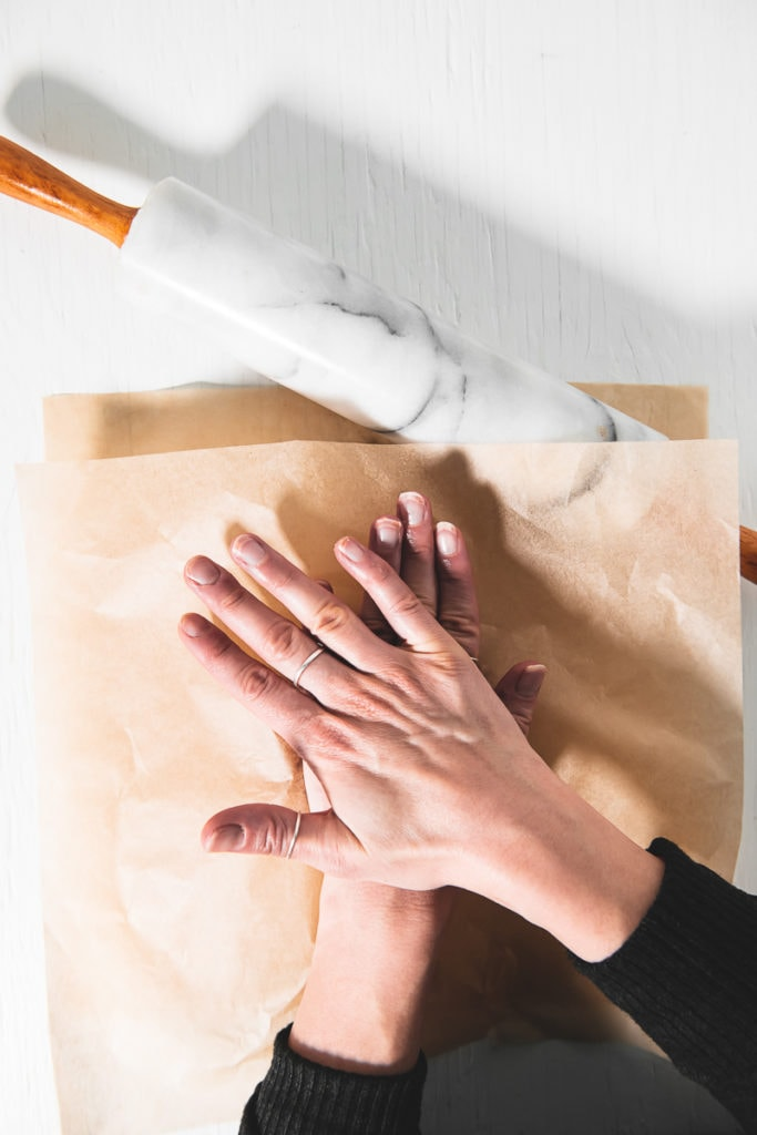 Hands pressing down a ball of Gingerbread cookie dough in between two pieces of parchment paper, with a rolling pin above.