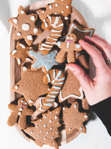 A hand grabbing a vegan gingerbread man from a plate full of crunchy gluten-free gingerbread cookies decorated with naturally coloured icing