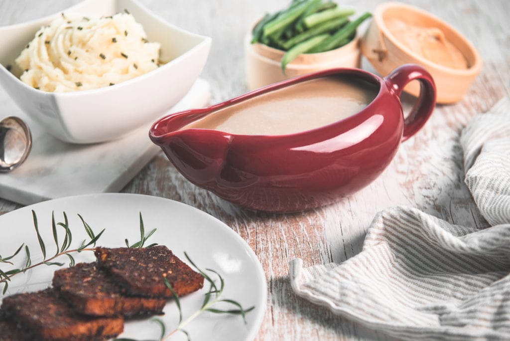 Mushroom gravy in a red gravy boat surrounded by mashed potatoes, green beans and a plate of roasted tempeh