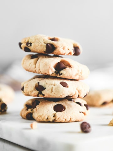 A stack of golden-brown chocolate chip cookies surrounded by crumbs and chocolate chips.