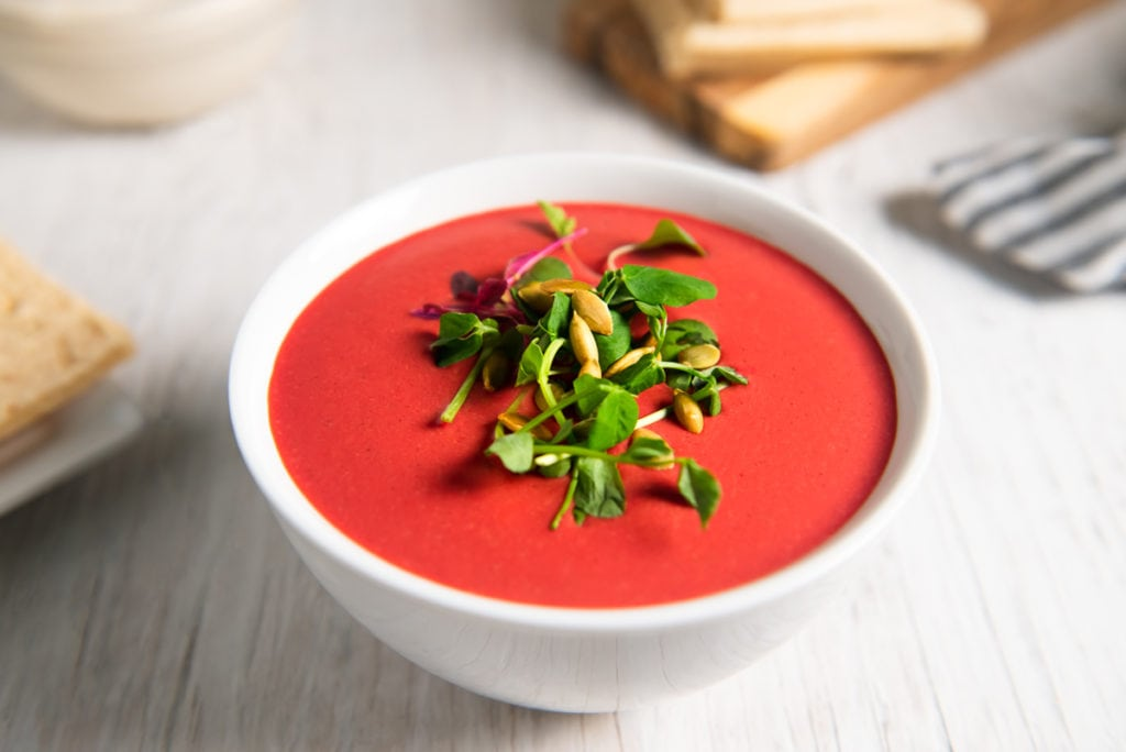 A bowl of vibrant, creamy beetroot soup garnished with fresh sprouts and pumpkin seeds.