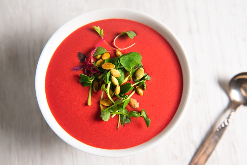 A bowl of creamy, beet soup garnished with fresh sprouts and pumpkins seeds, with a silver spoon sitting beside.