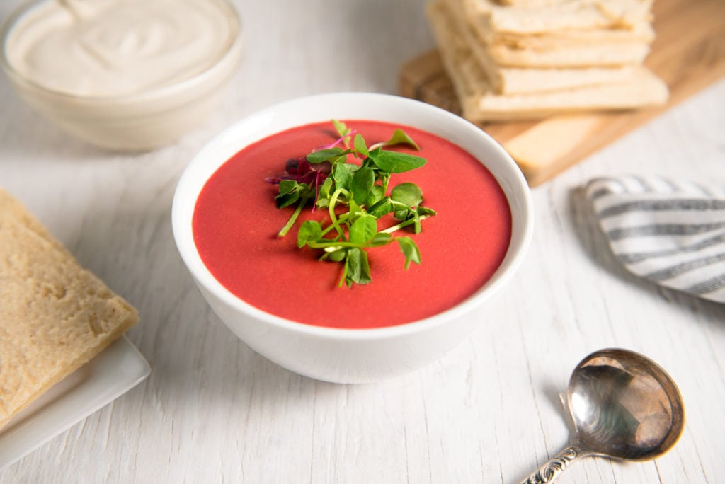 A bowl of vibrant, creamy beetroot soup garnished with fresh sprouts and pumpkin seeds in front of a stack of flatbread and bowl of cashew cream.