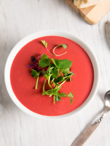 Vibrantly coloured vegan beet soup, garnished with fresh sprouts.