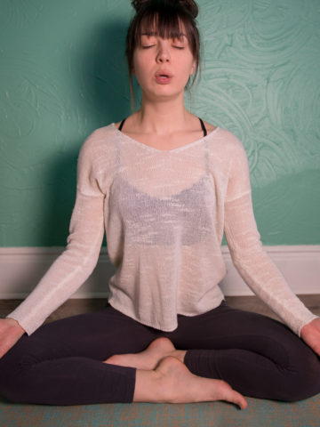 A woman sitting cross-legged on the floor in a meditation position, breathing heavily out of her mouth.