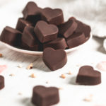 A plate piled full of heart-shaped chocolate truffles surrounded by more truffles, hazelnut crumbs and a linen cloth.