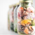 Four large mason jars full of frozen vegetable scraps for making vegetable broth, sitting in a diagonal line with the front jar in focus.