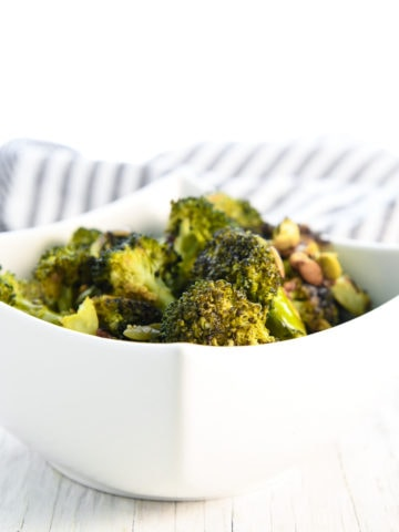 A bowl of roasted broccoli in a white square bowl with a striped linen cloth behind.