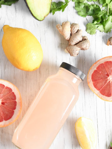 A bottle of grapefruit juice facing up surrounded by two grapefruit halves, a lemon and greens.
