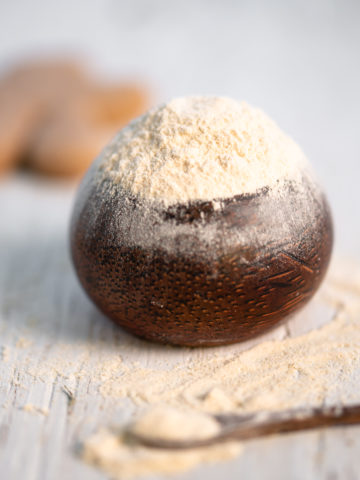 A small wooden bowl overflowing with powdered natural sugar with a spoon and spilt sugar sitting in front.