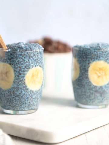 Two small glass pudding cups filled with Blue Majik chia pudding and banana slices, sitting on a marble cutting board with a white and grey linen napkin to the left and a bowl of nuts in the background.