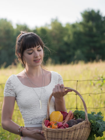 A girl holding a basket of fresh vegetables, looking very happy and healthy.