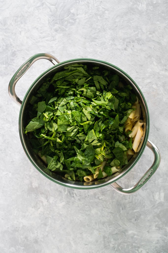 A large saucepan filled with penne pasta mixed with nutritional yeast, turmeric and apple cider vinegar with a heap of chopped spinach on top.