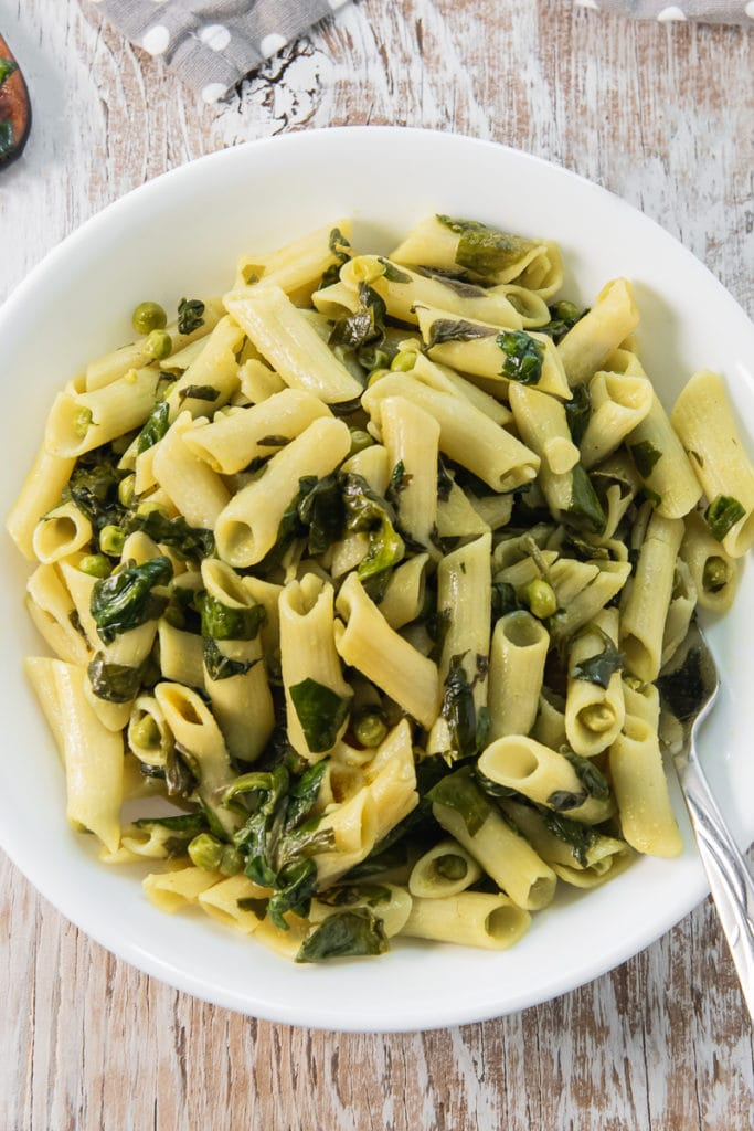 A close up of a heaping bowl of delicious Spinach and Peas Penne Pasta with a fork in the bowl.