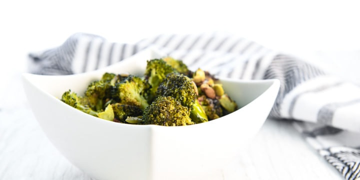 Roasted broccoli and pumpkin seeds in a white square bowl on a white washed tabletop with a grey and white striped linen napkin placed behind the bowl.