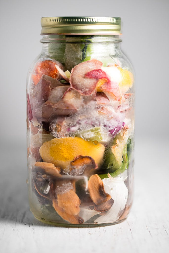 A large mason jar full of icy, frozen vegetable scraps on a white-washed table top.