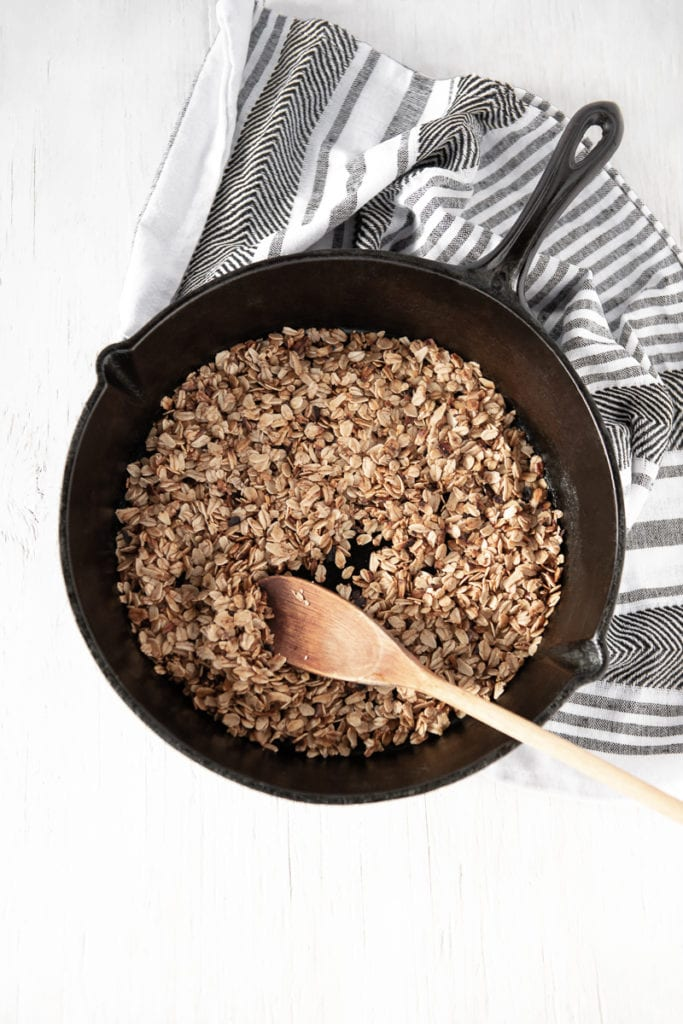 Golden-brown granola and a wooden spoon in a cast iron pan, on a white wooden table top with a grey and white striped linen cloth dropped underneath the handle of the skillet.