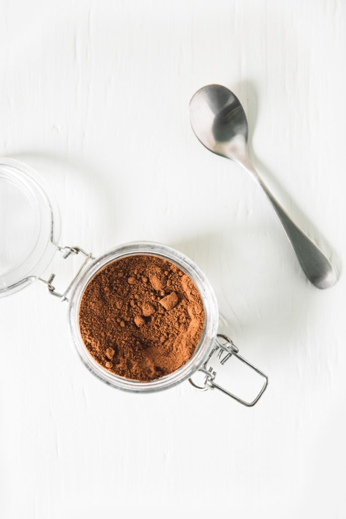 A birds eye view of an open jar , filled with Homemade French Vanilla Cappuccino Mix, and a spoon to the side