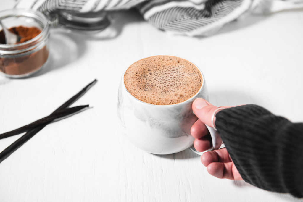 A hand grabbing a frothy french vanilla cappuccino, with two fresh vanilla beans and an open jar of Homemade Instant Cappuccino Powder