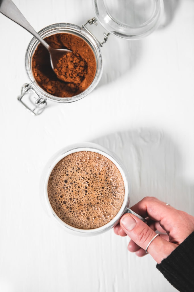 A hand grabbing a frothy french vanilla cappuccino and a jar of homemade french vanilla cappuccino mix with a spoon sticking out