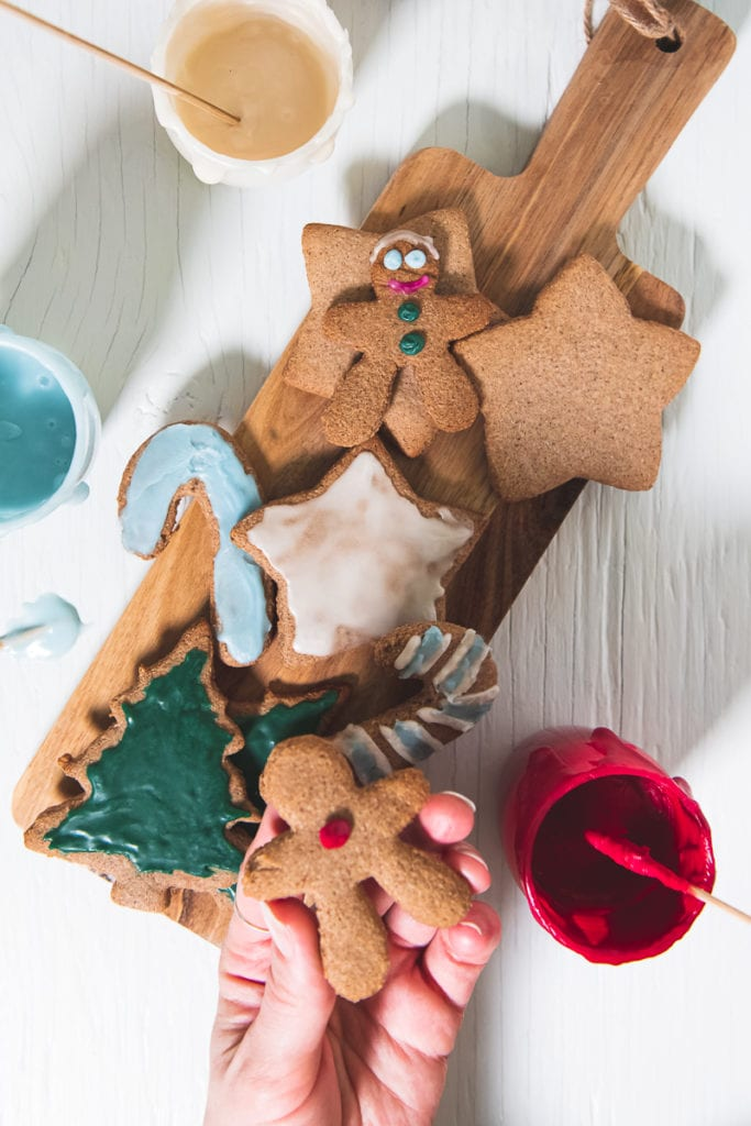 Crunchy Gluten-free Gingerbread Cookies being decorated with eggless royal icing