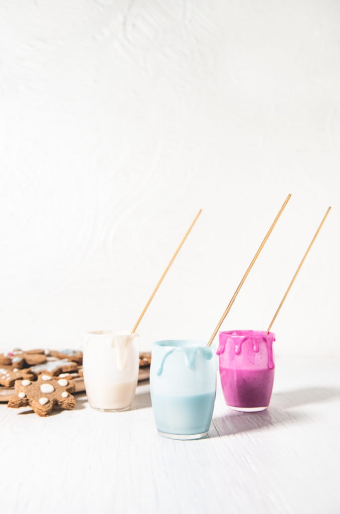 Three jars of naturally coloured icing with decorating sticks and icing dripping down the sides and a plate of gingerbread cookies beside.