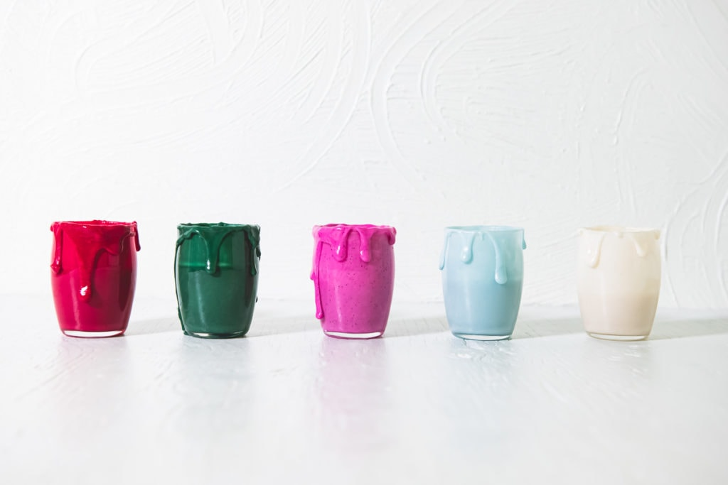 A row of five jars filled with homemade, naturally coloured icing (red, green, pink, frosty blue and white)