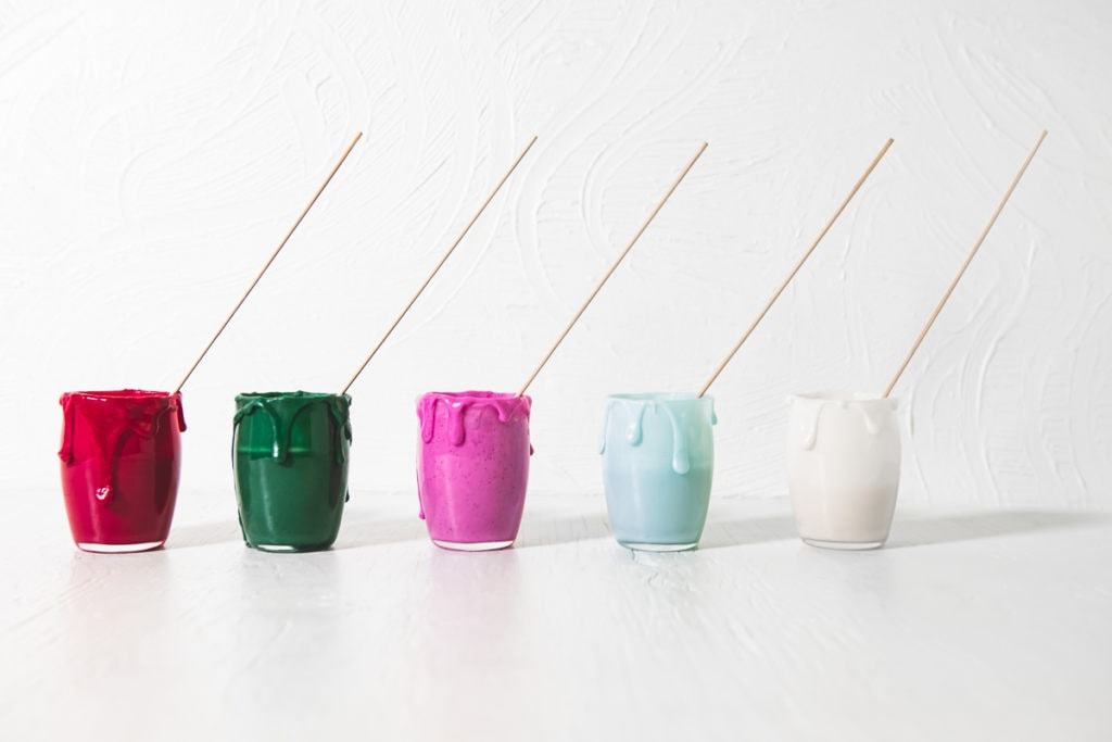 A row of homemade, naturally coloured icing (red, green, pink, blue and white) in jars with icing dripping down the sides and decorating sticks in each.