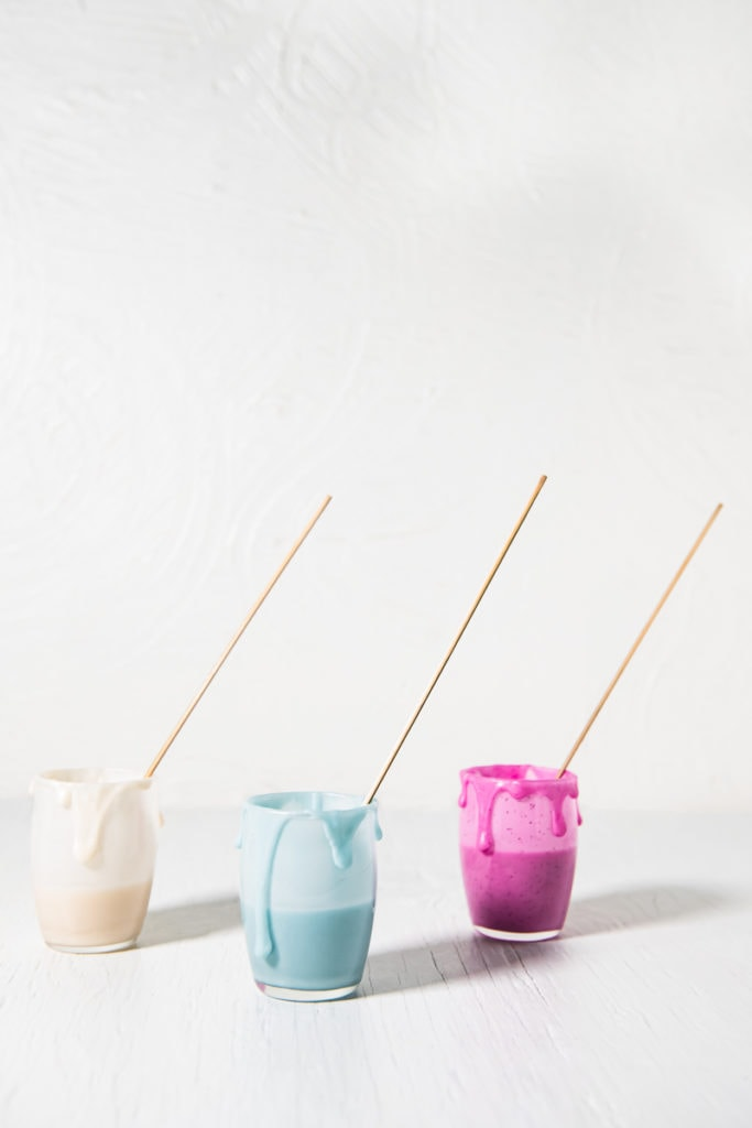 Three Jars of icing that's Naturally coloured (White, blue and pink) with icing dripping down the sides and a decorating stick in each jar.