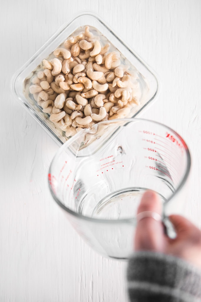 Water being poured from a liquid measuring cup into a glass container full of raw cashews.