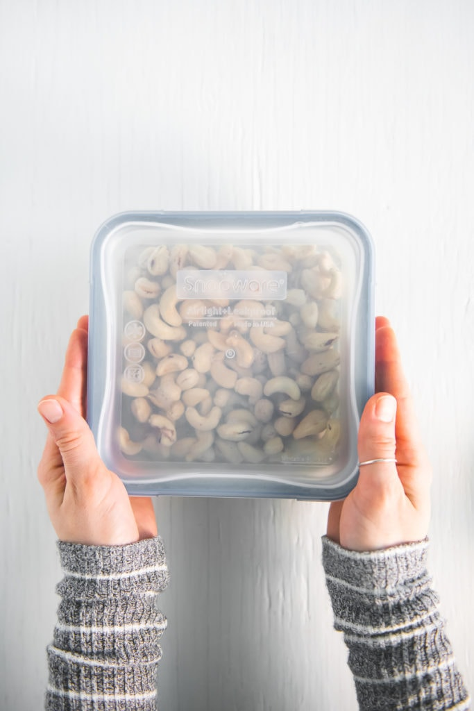 Hands grabbing a sealed glass container full of cashews soaking in water on either side.