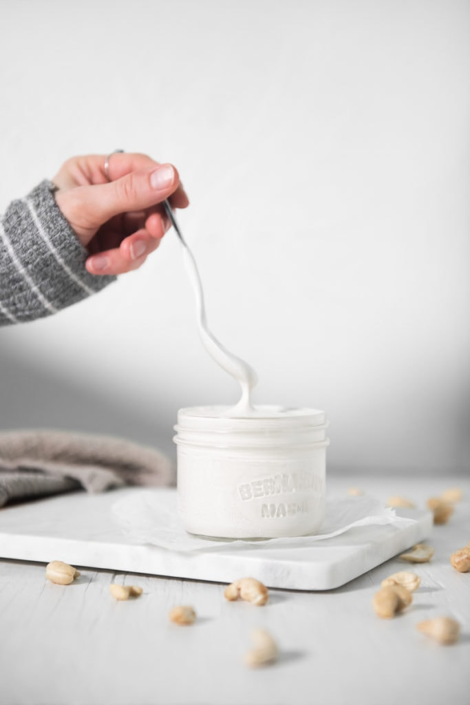 A hand lifting a spoon out of a jar full of cashew cream. The cashew cream dripping off the spoon back into the jar.