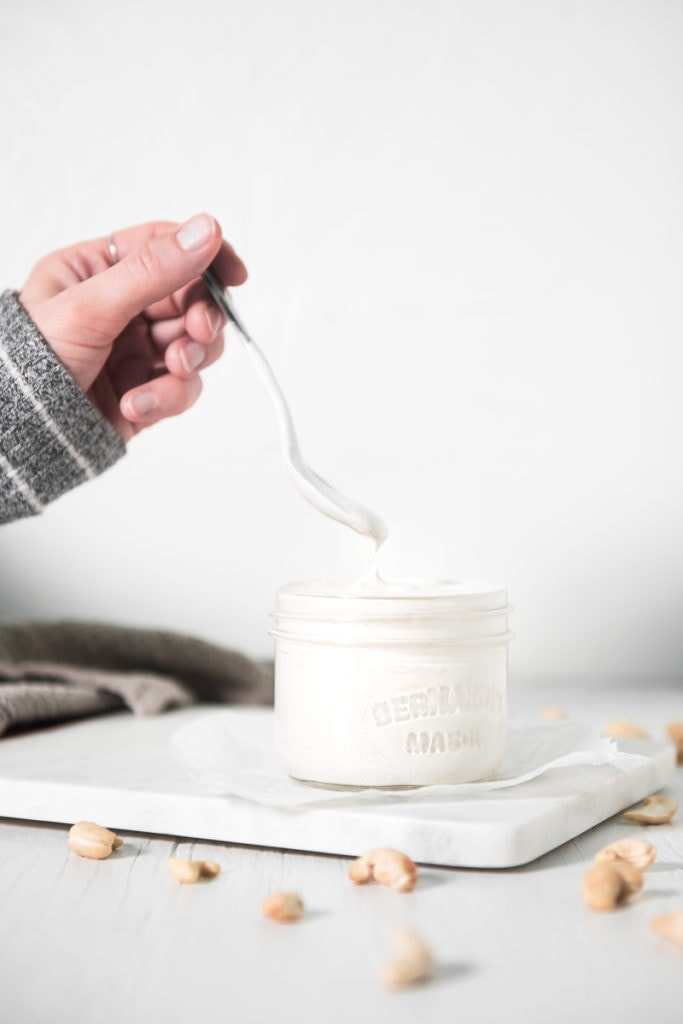 A hand lifting a dripping spoon out of a  full jar of cashew cream beside a linen cloth and raw cashews sprinkled around.