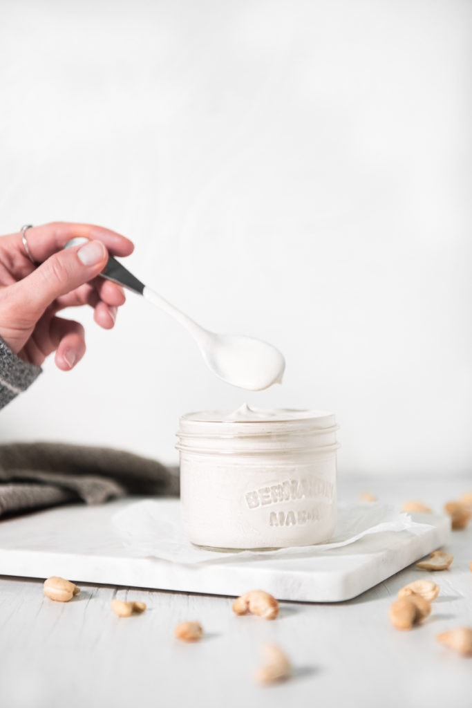 A hand dipping a spoon into a jar of cashew cream with raw cashews sprinkled around.