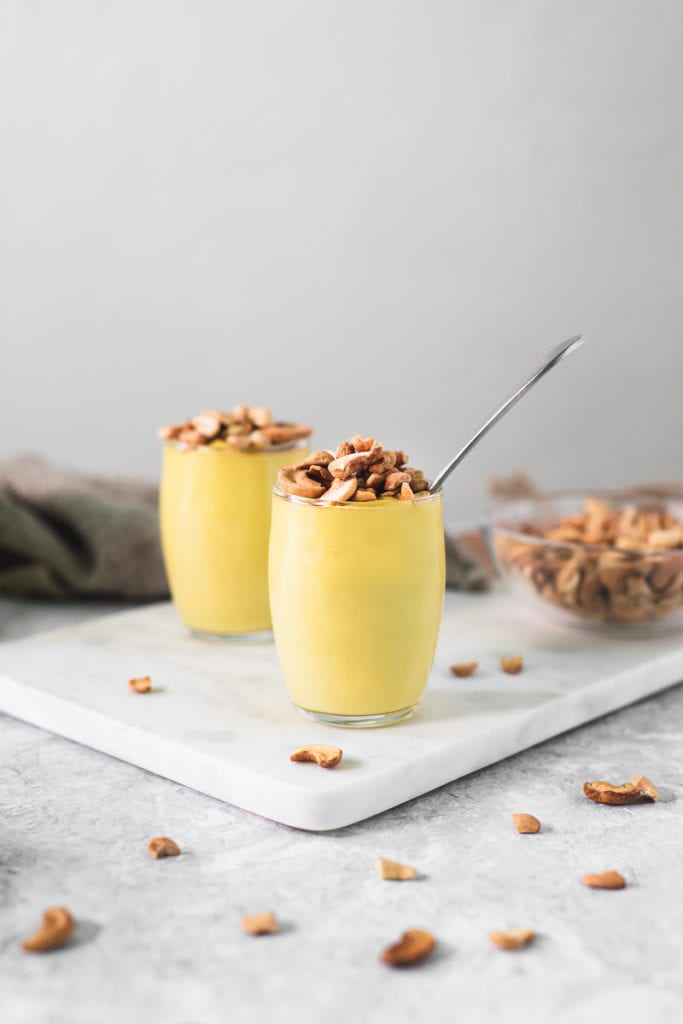 Two cups of banana yellow pudding topped with toasted cashews. The pudding cups are surrounded by dropped cashews pieces, a bowl of cashews and a linen cloth.