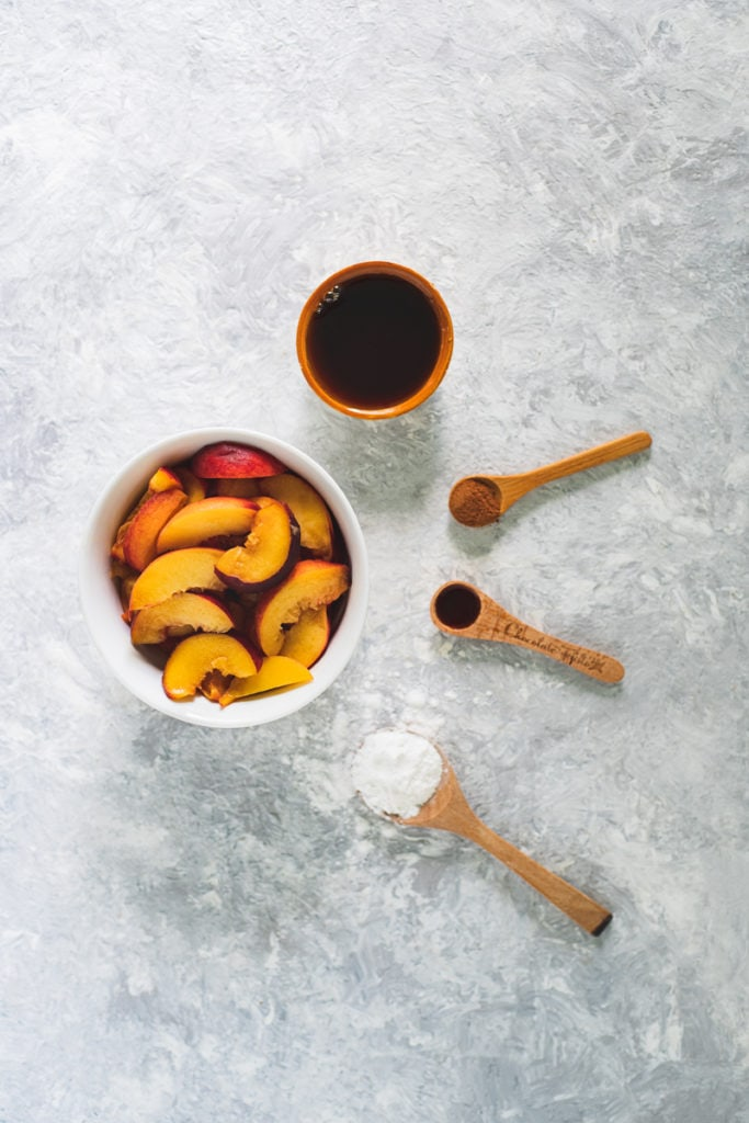 A bowl of freshly sliced peaches with a bowl of maple syrup and spoonfuls of arrowroot, vanilla extract and cinnamon surrounding in a half circle.